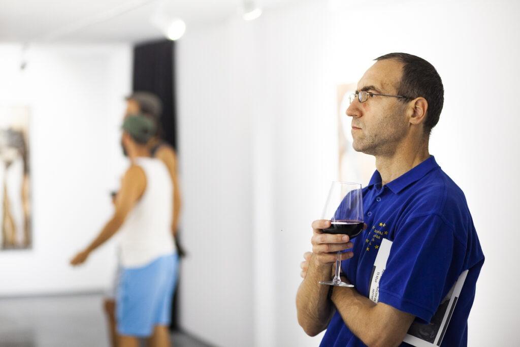 Męzczyzna z winem ogladający obraz