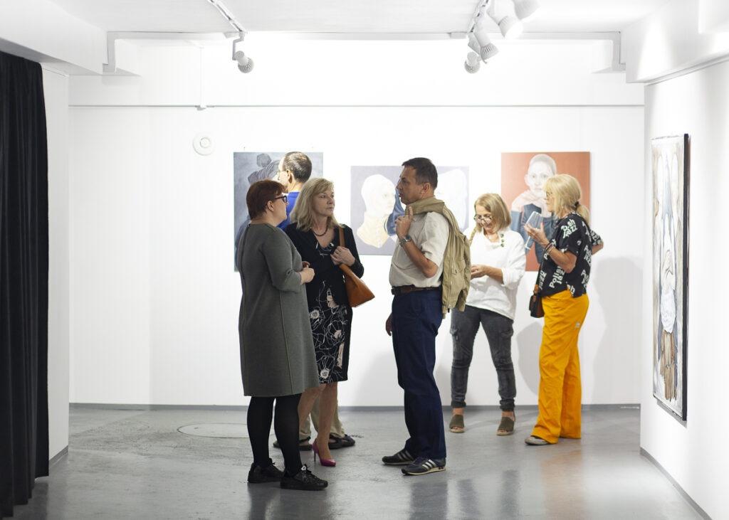 Grupa ludzi na otwarciu wystawy w galerii sztuki