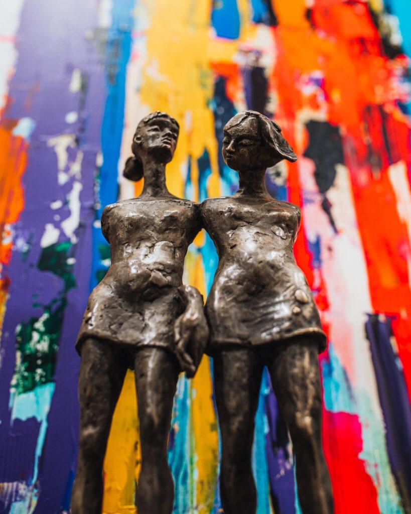 """Magdalena Karłowicz - rzeźba """"Siostrzeństwo"""" na tle kolorowego obrazu"""